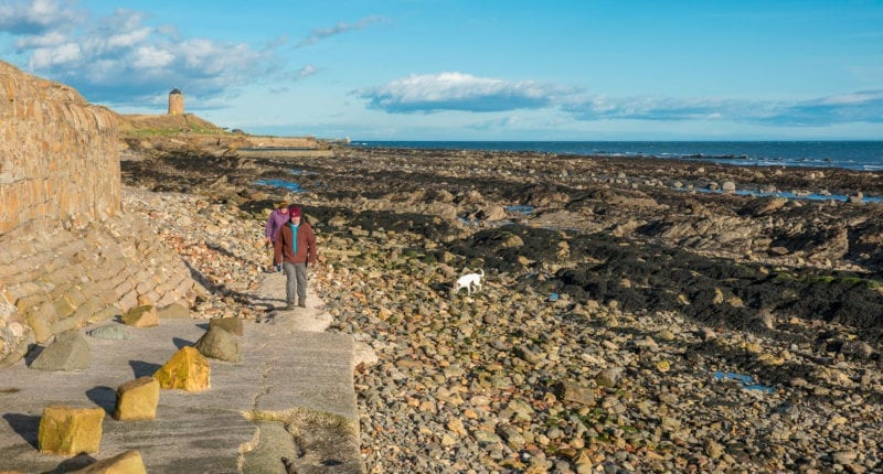 Walkers on the beach at St Monans with the St Monans Windmill seen in the background