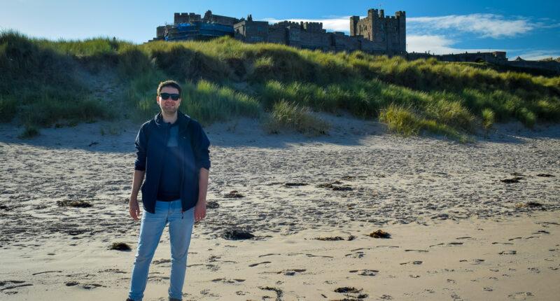 Northumberland Coast Path walker at Bamburgh Castle