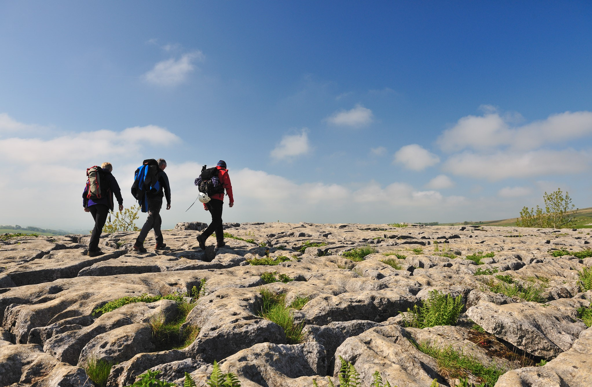 Walkers on the limestone pavement above the cliffs of Malham Cove