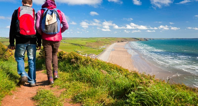 Couple walking on the trail with Newgale beach in distance