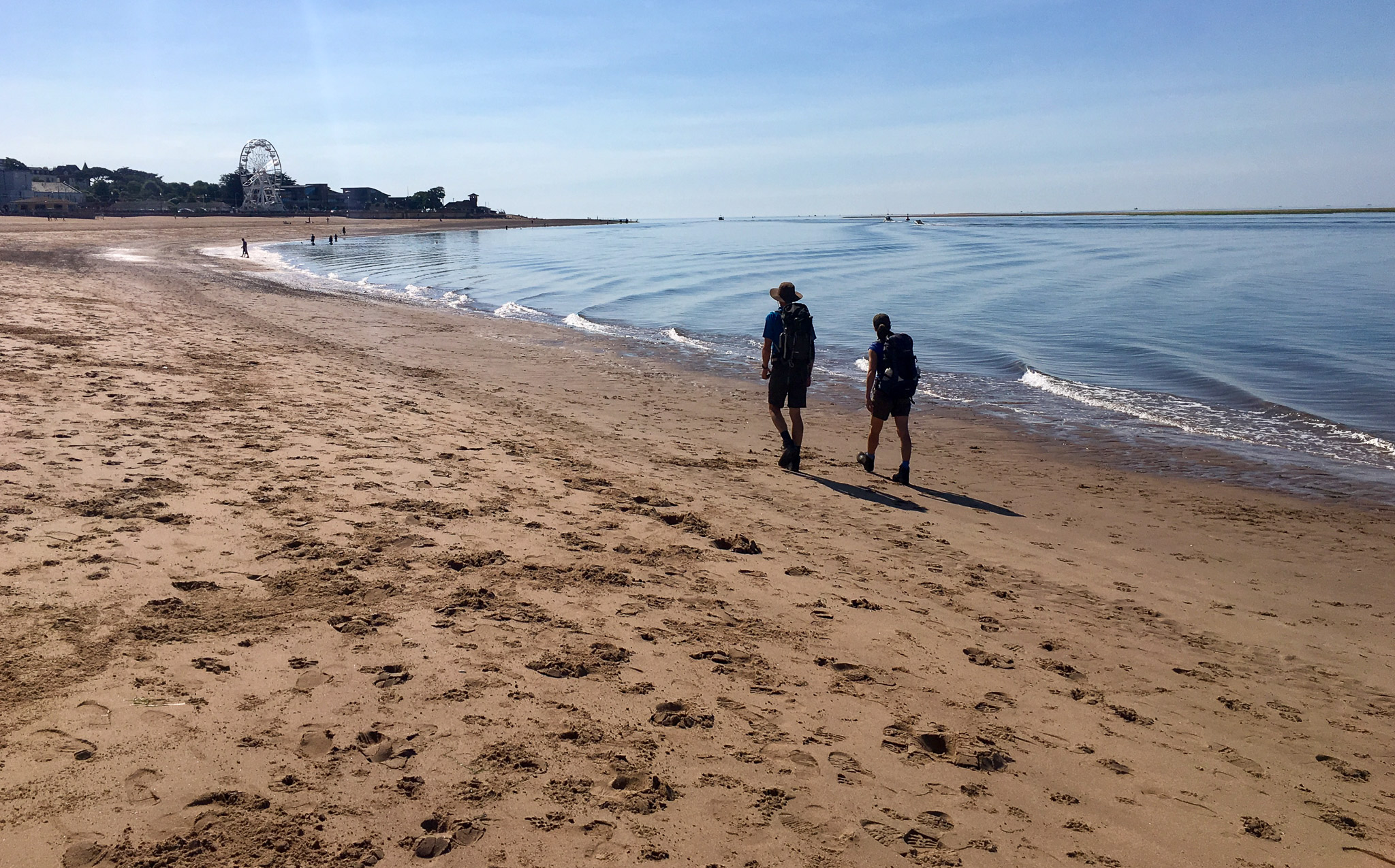 Hikers walking on the beach on the South West Coast Path