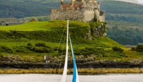 A yacht passes Duart Castle On The Isle Of Mull