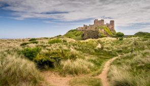 Bamburgh Castle through the sand dunes